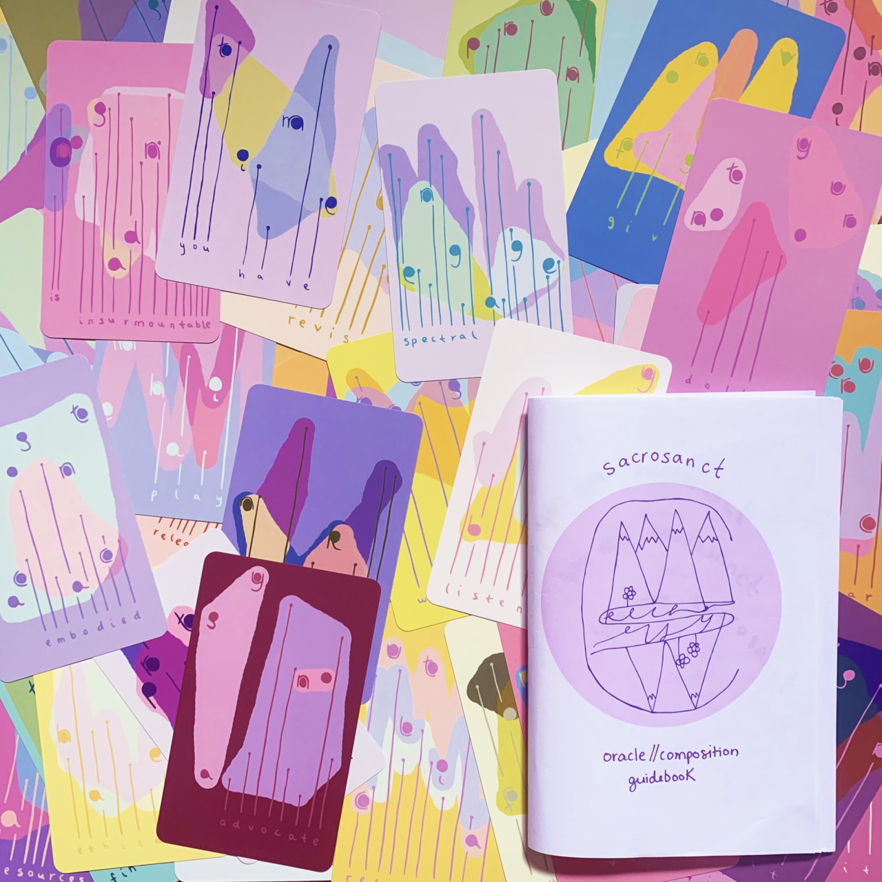 A multi-pastel-colored collection of Sacrosanct Oracle//Composition Cards are collaged. Among them is the Sacrosanct Oracle//Composition Guidebook.